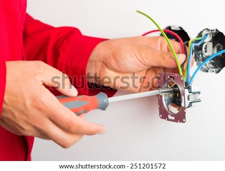 Electrician assembling new electrical outlet on wall.