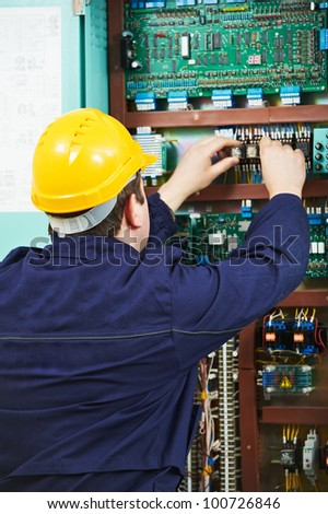 Electrician at safety fuse device replace work at electric power switch line box - stock photo