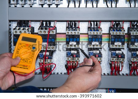 electrician at work with an electric panel - stock photo