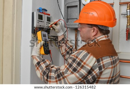 Electrician at work with his instrument of measurement. Model is actual electrician. - stock photo