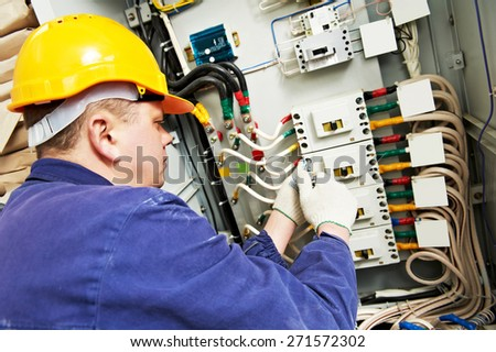 electrician builder at work with tester measuring high voltage and current of power electric line in electical distribution fuseboard - stock photo