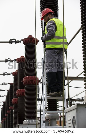Electrician builder engineer.Electricity transformer at a power plant.High voltage power station.Switches and breakers to operate the electric current.High voltage circuit breaker in power substation - stock photo
