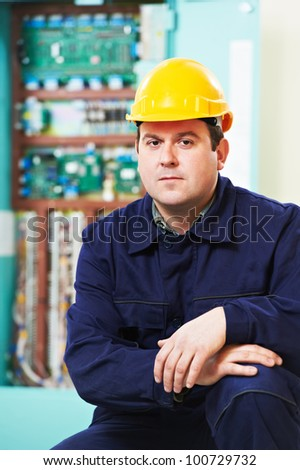 Electrician builder portrait over high voltage power electric line in industrial distribution fuseboard - stock photo