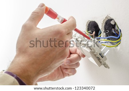 Electrician checking electric voltage on a light switch with neon-lamp tester.