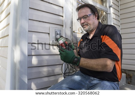 Electrician checking outside outlet for customer. - stock photo