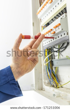 Electrician checking the wiring in the electrical supply box of a domestic house as he performs repairs, maintenance, during installation,or during an inspection for a compliance certificate