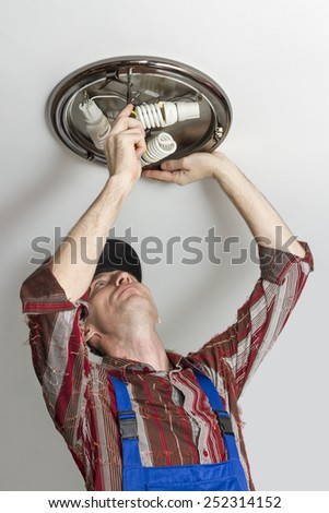 Electrician checks that secures the lamp from the ceiling. - stock photo
