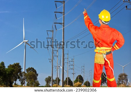 Electrician climbing ware and pointing at electric post power pole - stock photo