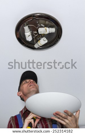 Electrician collects the lamp on the ceiling. - stock photo