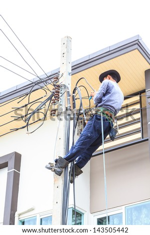 Electrician connects wires on a pole