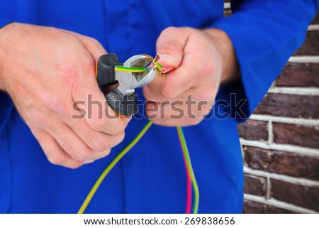 Electrician cutting wire with pliers against red brick wall - stock photo