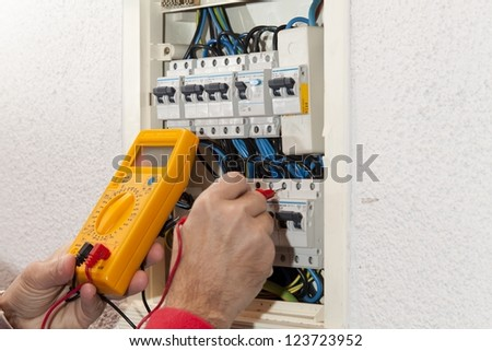 Electrician doing some checks on a light box - stock photo