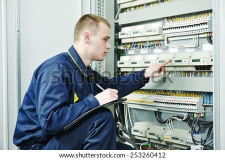 electrician engineer worker inspector  in front of fuseboard equipment in room - stock photo