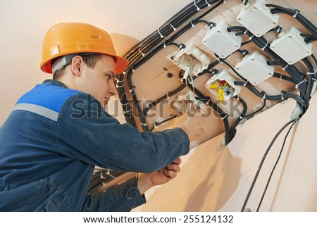 electrician engineer works with cables at distribution boxes in electric network - stock photo