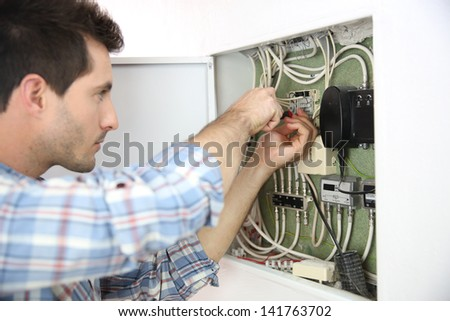 Electrician fixing cable in domestic electrical box - stock photo