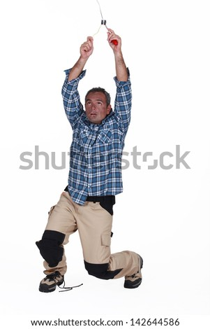 electrician fixing the installation and having an accident - stock photo