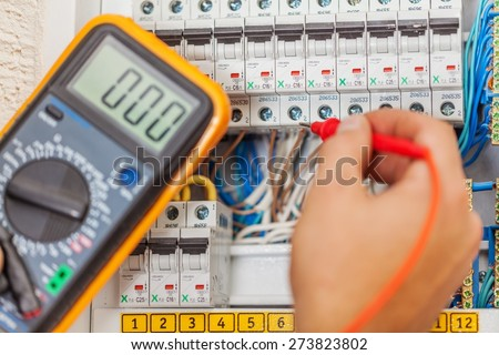 Electrician. Hand of an electrician with multimeter probe at an electrical switchgear cabinet - stock photo