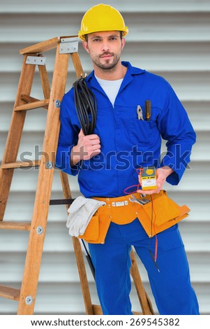 Electrician holding cables and multimeter against grey shutters - stock photo