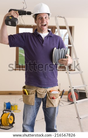 Electrician holding drill to head and making a face - stock photo