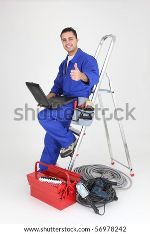 Electrician in overalls with a laptop computer on white background - stock photo