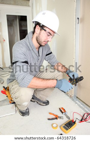 Electrician in room under construction
