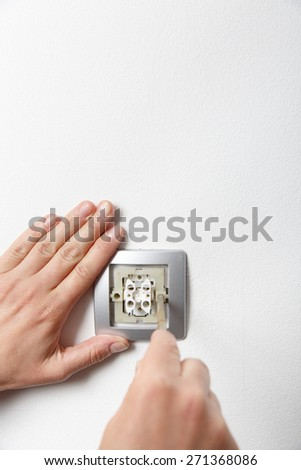 Electrician installing a silver light switch with a screwdriver on a white wall, renovating home.