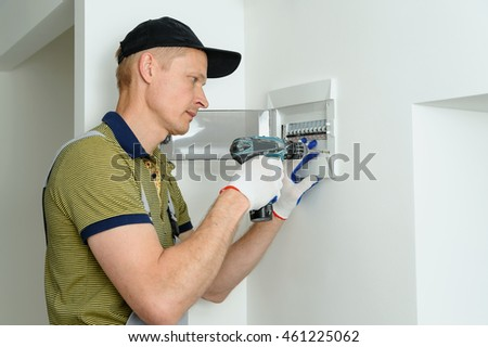 stock photo electrician installing an electrical fuse box in a house 461225062 electrician installing electrical fuse box house stock photo installing a fuse box at alyssarenee.co