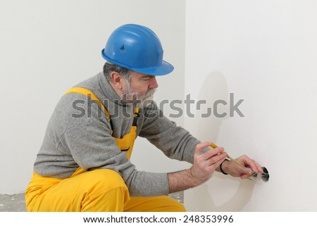 Electrician installing electrical plug at wall and using voltage testing screwdriver - stock photo