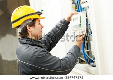 Electrician installing energy saving meter - stock photo
