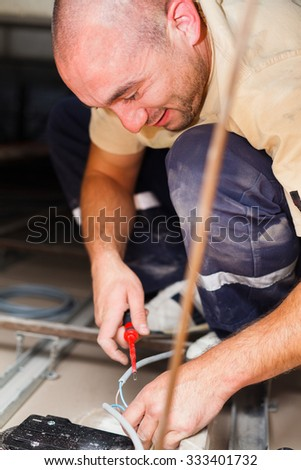 Electrician installing light in houses using tools and cords. - stock photo