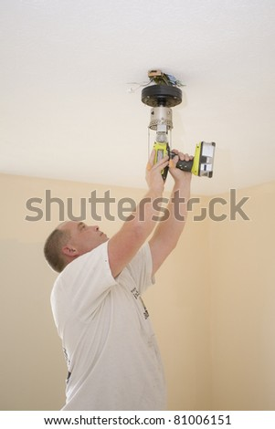Electrician installing new light fixture and fan - stock photo