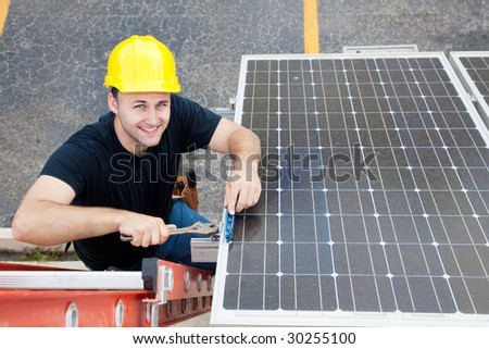 Electrician installing solar panels on the roof of a building. - stock photo