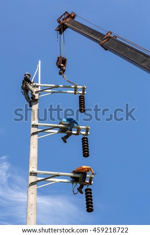 Electrician lineman workers compose ceramic electrical insulation on electric post power pole - stock photo