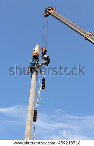 Electrician lineman workers pulled by a crane at climbing work on electric post power pole