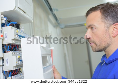 electrician looking at fusebox - stock photo