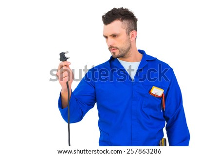 Electrician looking at plug on white background - stock photo