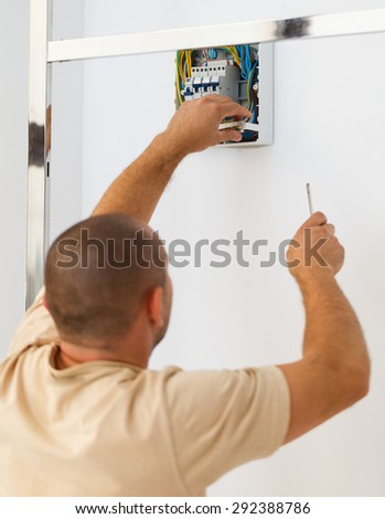 Electrician man installing electric fuse at home. - stock photo