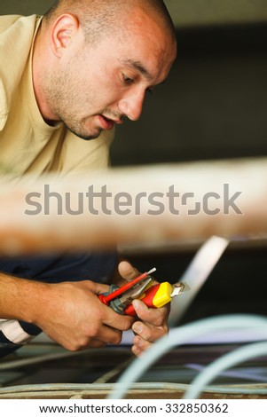 Electrician man working with wires mounting lights in house. - stock photo