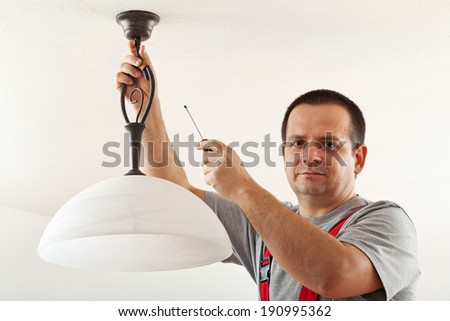 Electrician mounting ceiling lamp - closeup - stock photo