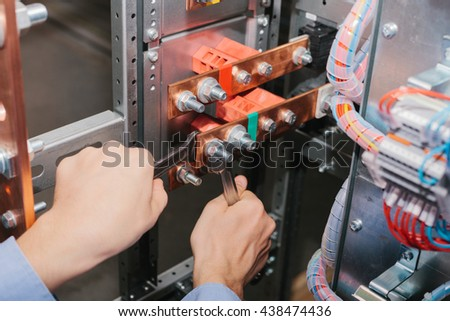Electrician near the low-voltage cabinet. Uninterrupted power supply. Electricity. - stock photo