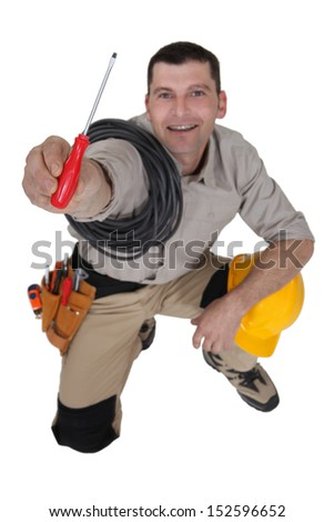 Electrician offering screwdriver - stock photo
