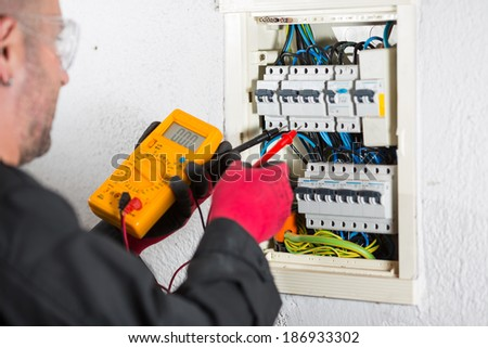 Electrician performing checks on a light box - stock photo