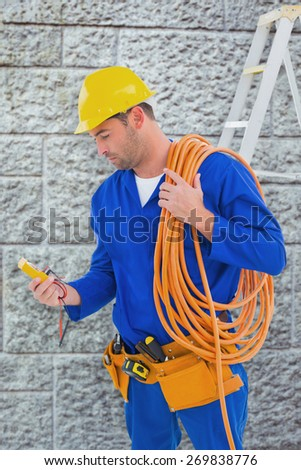 Electrician reading multimeter in bright office against grey brick wall - stock photo