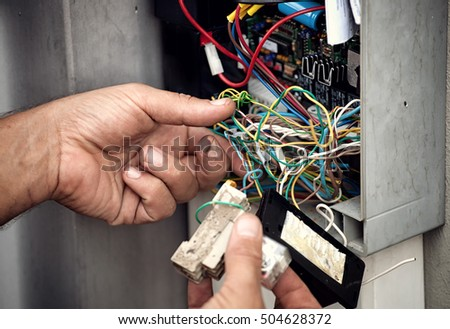 Electrician repairing electric system of an automatic gate.