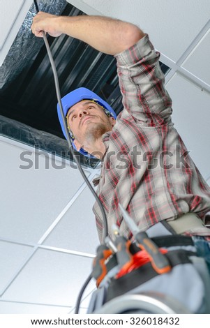 Electrician repairing wiring in an office - stock photo