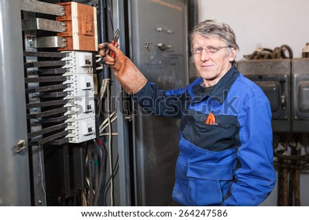 Electrician repairman in blue uniform holding pliers in rubber glove hand