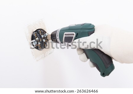 Electrician replacing old socket with cordless drill/driver - stock photo