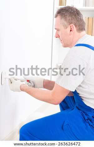 Electrician replacing old socket with pilers and screwdriver - stock photo