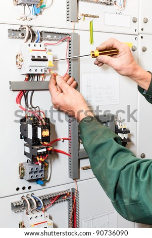 Electrician`s hands working with screwdriver in cables and wires - stock photo