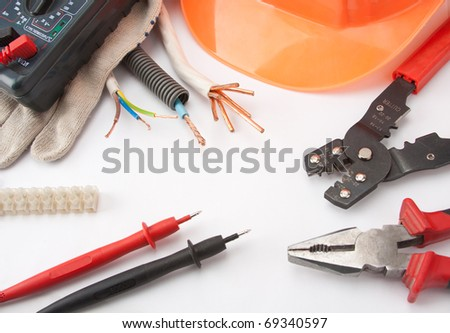 Electrician's tools. Hardhat, multimeter, pliers, cutter, cables, etc. - stock photo